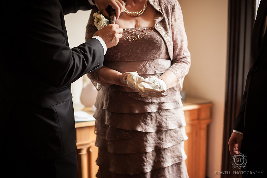 pinning the boutonniere on the mother of the bride