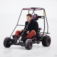 Son driving dune buggy in the snow